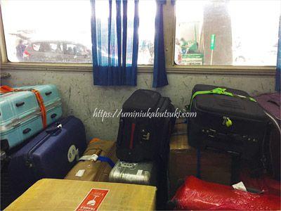 無料シャトルバスの中に積み上げられた旅行客の荷物