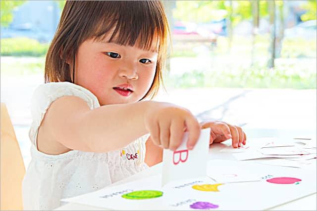 英単語のカードで遊ぶ乳児